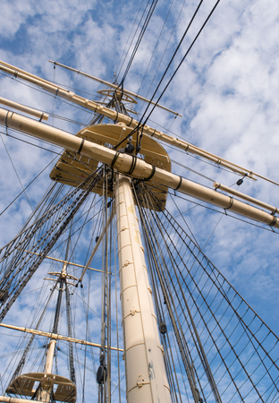 Wooden sail ship rigging against blue sky with clouds