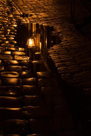 Vintage straat licht weerspiegelt in poedel op natte kasseien na regenval. Stockfoto