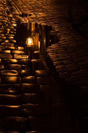 Vintage street light reflecting in poodle on wet cobblestone after rainfall. Imagens