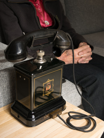 antique telephone: Grandma anticipating a call on the old black antique telephone Stock Photo