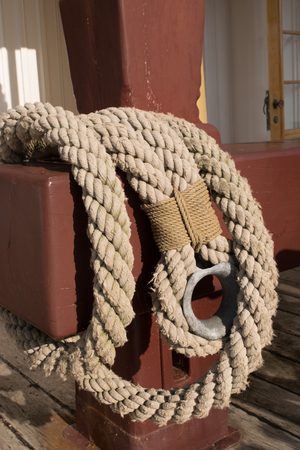 threadbare: Old worn rope on a red pole on a wooden sailship
