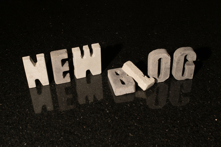 spelled: The words New blog spelled with grey concrete letters on black reflecting tile Stock Photo