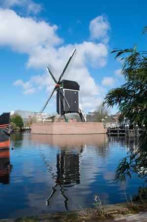 Dutch windmill reflecting in the river Rijn, Leiden, Netherlands Stock Photo