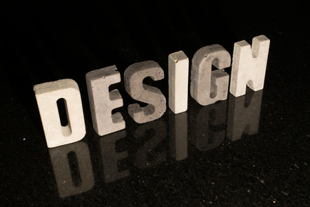 spelled: The word Design spelled with grey concrete letters on black reflecting tile