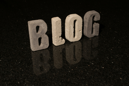 spelled: The word blog spelled with grey concrete letters on black reflecting tile Stock Photo
