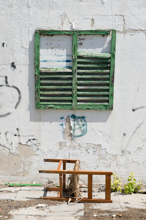 worn: Worn building facade with green shutters.