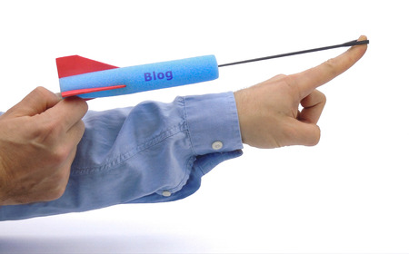 Conceptual or abstract illustration of launching a new blog by shooting a foam arrow with the word blog.