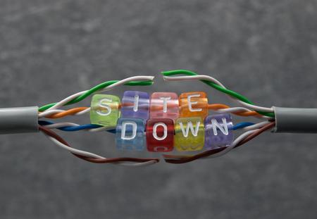 Tekst in kleurrijke parels. Site omlaag voor website onderhoud met gebroken kabel en grijze achtergrond. Stockfoto