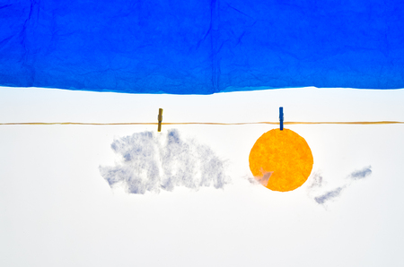 pegs: composition with blue sky clouds and sun made with tissue paper, a rope, small pegs for hanging the laundry