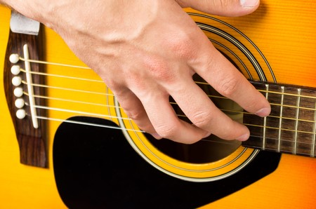 close up of a male hand playing acoustic guitar Stock Photo