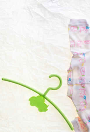 baby wardrobe: colored hanger, coat rack for infants clothing Stock Photo