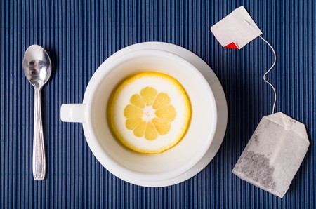 tea filter: simple composition with tea cup empty but with slice of lemon, saucer and spoon, filter bag of tesu blue striped background