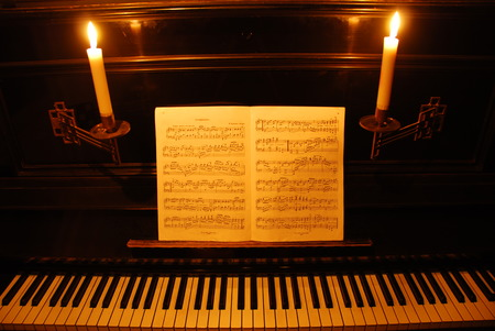 ivories: Antique black piano with burning candles and note sheets
