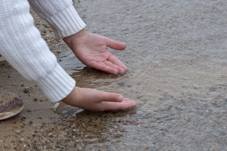 Childs hands feeling the water