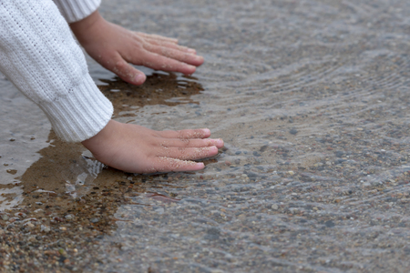 Childs hands touching the water Stock Photo