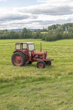 Red tractor in farming landscape