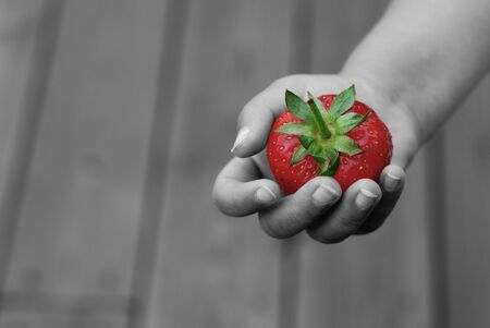 Strawberry in toddlers hand on grey background