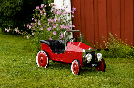 licence: A bright red toy car covered in raindrops in a garden outside a house. The licence plate reads 1938. The car is old-fashioned, probably from the 1930-s. The back wheels of the car are bigger than the front ones. There are raindrops on the surface of the c