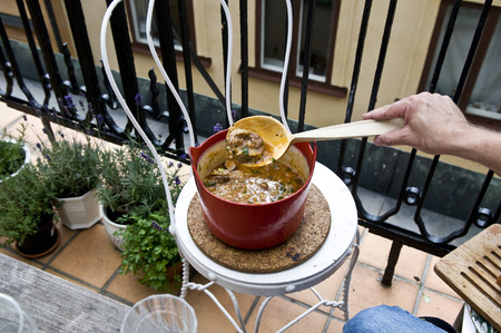 big cork: A red pot of meat stew being stirred with a big wooden spoon. The pot is on a round cork hot pot stand, on a white chair on a balcony. There are some potted plants on the balcony floor. Stock Photo