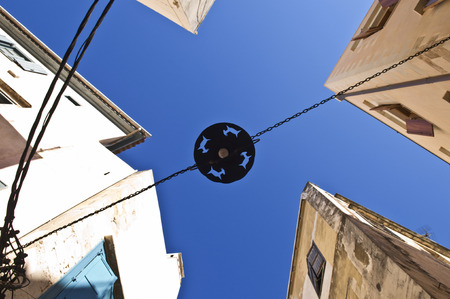 mountain goats: A metal street lampshade hanging on chains against the blue sky in a street in Chania, Crete, Greece. Kri-Kri mountain goats are a symbol of Crete. Stock Photo