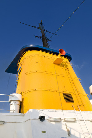 Yellow ship funnel with a red speaker on side. There are ladders around the funnel and some ventilation grids in it.