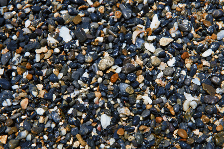 seashore: Wet stones on the seashore. They are black, grey, pink, yellow, and off-white.