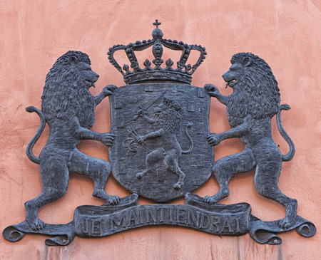 motto: A coat of arms on a wall in Stockholm, showing two lions holding a shield with a third lion on it and a crown. The motto Je Maintiendrai is the motto of the House of Orange and Nassau, the Royal Family of the Netherlands.