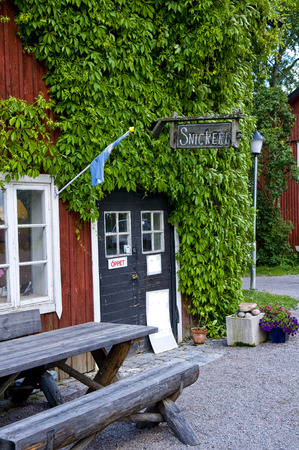 woodwork: A small old-fashioned countryside woodwork shop near Uppsala, Sweden. The walls of the workshop are painted red with traditional Falu red paint. There is a sign with the word Snickeri woodwork written in chalk above the door. The sign on the door says  Editorial