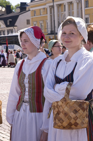 birchbark: June 20, 2010. Helsinki, Finland. Two women wearing traditional clothes is taking part in the Traditional Culture Festival. One woman is carrying a birchbark basket. Editorial