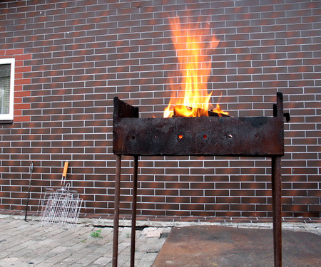 Firewood and fire in the old rusty charcoal grill on a brick wall background
