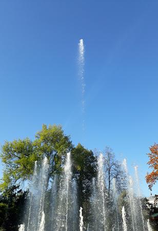 jet stream: Chorros urbanos de la fuente en el fondo de los árboles del otoño y del cielo azul. Humor otoñal
