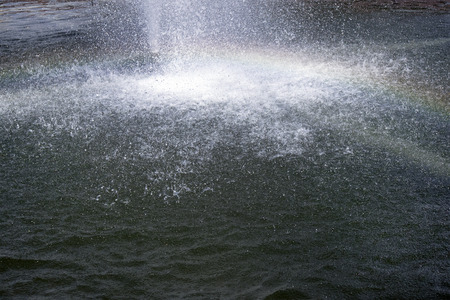 Small spray of water jet falling down into the fountain reservoir and the rainbow in the foreground