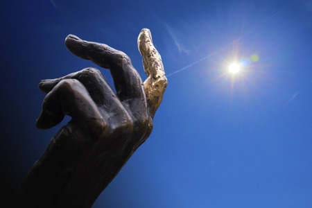 Hand of bronze statue with a finger pointing to the sky, concept of a collage against a blue sky and sun with aureole