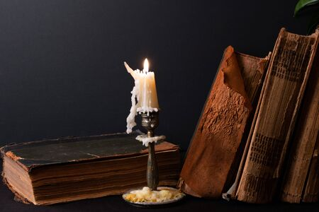 Stack of ancient books with yellowed shabby pages and candlestick with lighted candle