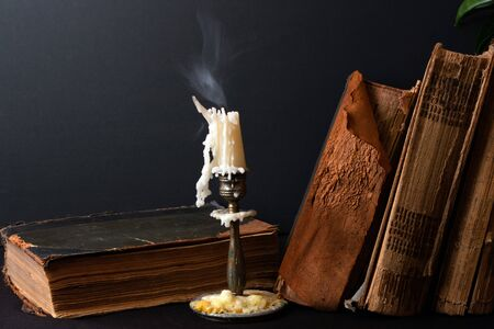 Stack of ancient books with yellowed shabby pages and candlestick with steaming candle