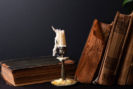 Stack of ancient books with yellowed shabby pages and bronze candlestick with candle