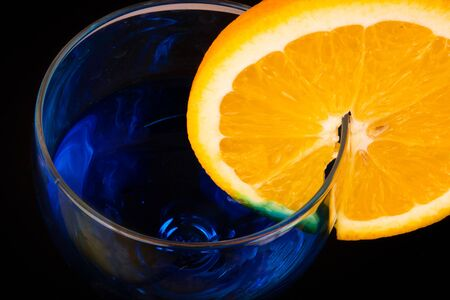 Top of the glass with blue beverage and slice of juicy orange on the side