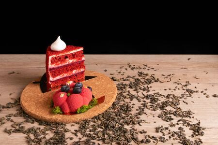 Two appetizing delicious red cakes on a cork stand with scattered dry green tea