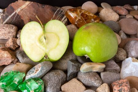 Halves of big green apple lying on pebble decorated with agate, jasper and colored glass
