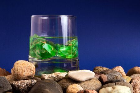 Glass with water and two green gemstones inside standing on a pile of pebble