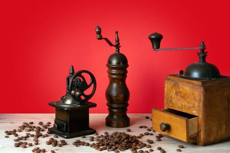 Wooden vintage manual coffee mills and pepper mill with coffee beans scattered on a wooden surface Фото со стока