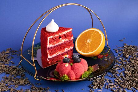 Two appetizing delicious red cakes and half of juicy orange on a glass plate with scattered dry green tea