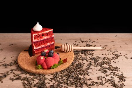 Two appetizing delicious red cakes and honey dipper on a cork stand with scattered dry green tea on a wooden board