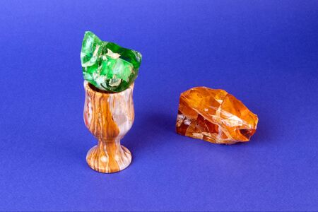 Small elegant onyx glass with green gem inside and piece of raw amber isolated on violet background