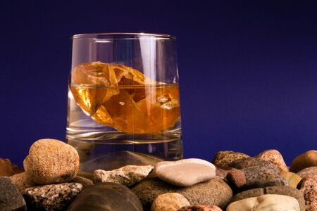 Glass with water and piece of amber inside standing on a pile of pebble Фото со стока