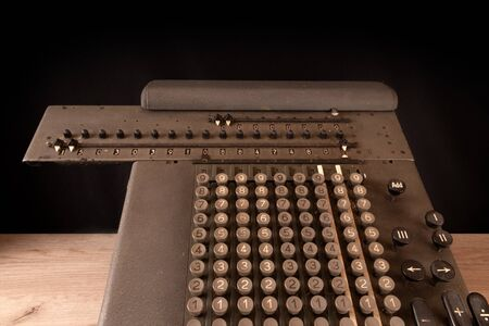 Old counting mechanism, dusty vintage arithmometer standing on a wooden board against black fabric