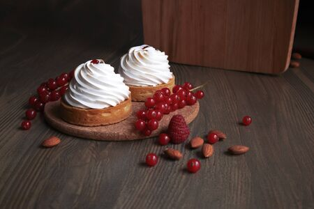 Two cupcakes with whipped cream, fresh red currant bunch and scattered almond nuts on the wooden table Фото со стока