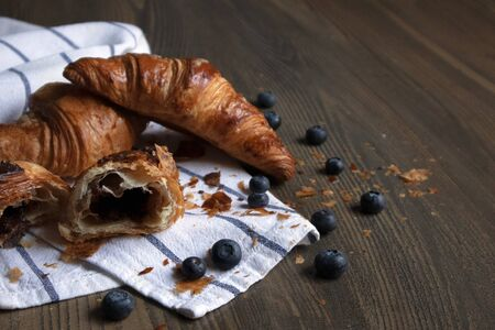 Few appetizing ruddy croissants with filling and blueberries lying on a striped towel against wooden table