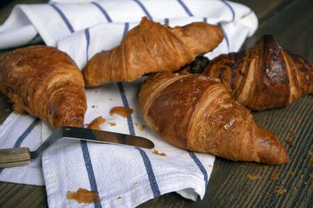 Few appetizing ruddy croissants and pastry knife lying on a striped towel against wooden table