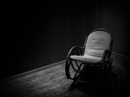 Wicker rocking chair in empty room with wooden floor, monochrome minimalist style Фото со стока